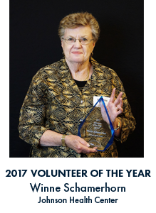 Winner Schamerhorn holding award with blue font under her picture reading 2017 Volunteer of the Year Winne Schamerhorn Johnson Health Center